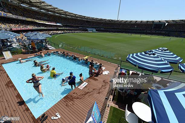 Spectators watch the first day-night cricket Test between Australia and Pakistan from the wading pool inside the Gabba stadium in Brisbane on...