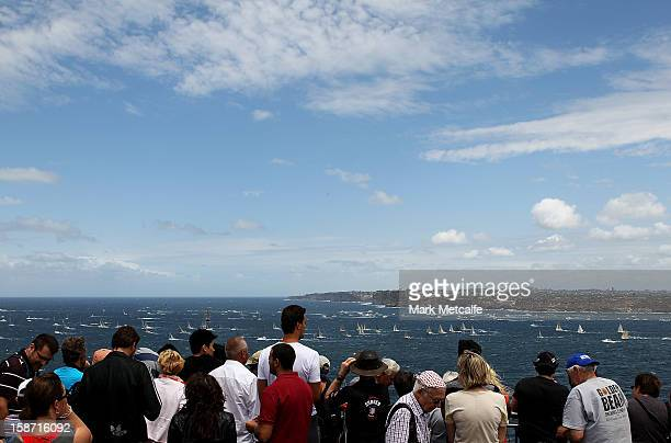 Spectators watch the fleet head out to sea during during the 2013 Sydney to Hobart on Sydney Harbour on December 26 2012 in Sydney Australia