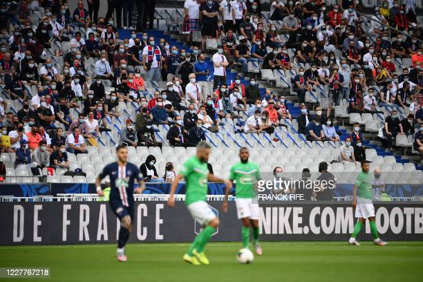 Spectators watch the French Cup final football match between Paris Saint-Germain and Saint-Etienne on July 24 at the Stade de France in Saint-Denis,...
