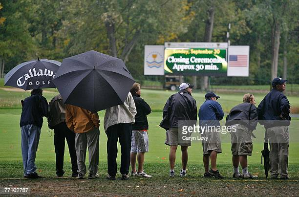 Spectators watch the golf in the rain during the second round of competition for The Presidents Cup on September 28 at The Royal Montreal Golf Club...