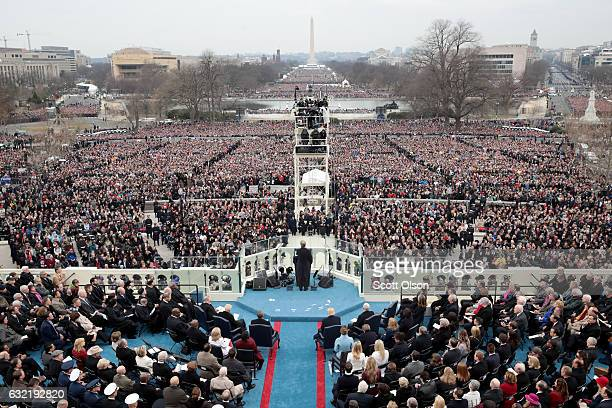 Spectators watch the inauguration proceedings on the West Front of the US Capitol on January 20 2017 in Washington DC In today's inauguration...