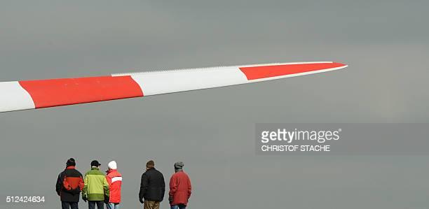 Spectators watch the installation of the rotor blades of a wind turbine near the small Bavarian village of Sindersdorf near Nuremberg southern...
