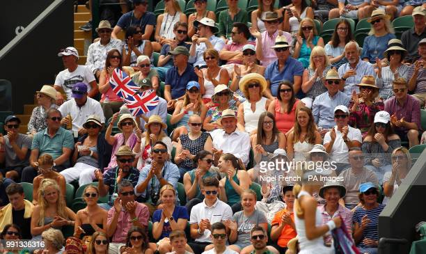 Spectators watch the match action between Katie Swan and Mihaela Buzarnescu on day three of the Wimbledon Championships at the All England Lawn...