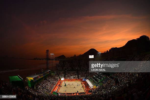 TOPSHOT Spectators watch the men's beach volleyball qualifying match between the Netherlands and Russia as the sun sets over Copacabana's Beach...