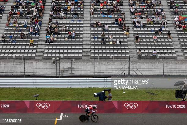 Spectators watch the men's cycling road individual time trial during the Tokyo 2020 Olympic Games at the Fuji International Speedway in Oyama,...