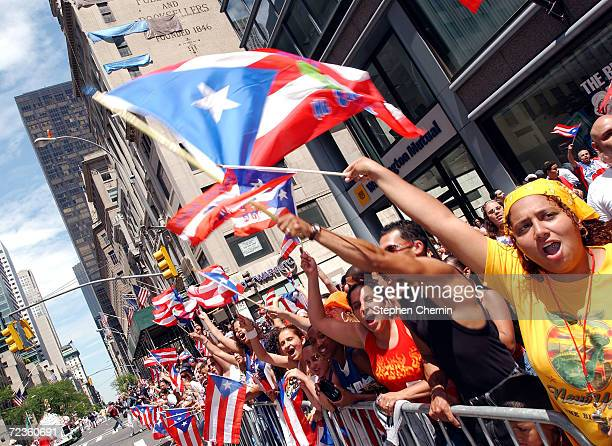 Spectators watch the ninth annual Puerto Rican Day Parade pass by June 13 2004 in New York City Tens of thousands of people lined Fifth Avenue for...