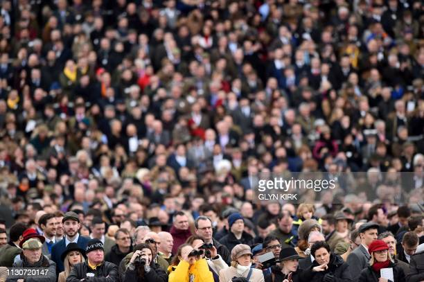 Spectators watch the riders in the Albert Bartlett Novices' Hurdle race on the final day of the Cheltenham Festival horse racing meeting at...