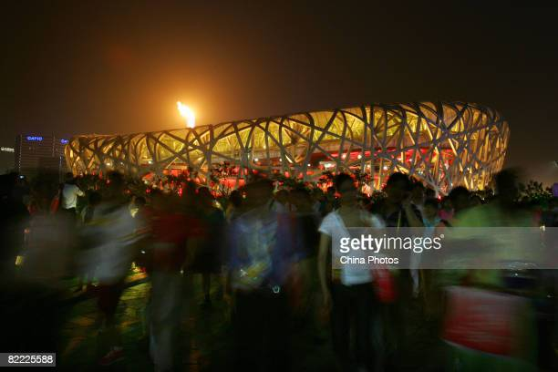Spectators watch the shining Olympic flame outside the National Stadium during the Opening Ceremony for the Beijing 2008 Olympic Games on August 8...
