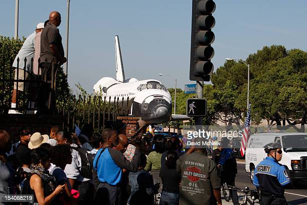 Spectators watch the space shuttle Endeavour pass by as it is transported from Los Angeles International Airport to the California Science Center in...