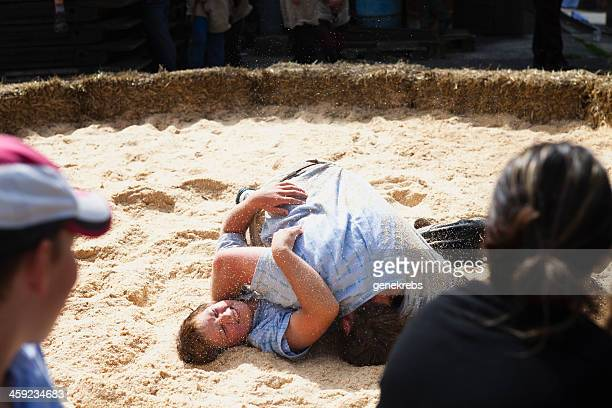 spectators watch their friend lose a friendly wrestling match. - rough housing stock photos and pictures