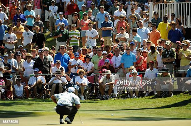 Spectators watch Tiger Woods line up a putt on the 13th green during the third round of THE PLAYERS Championship on THE PLAYERS Stadium Course at TPC...