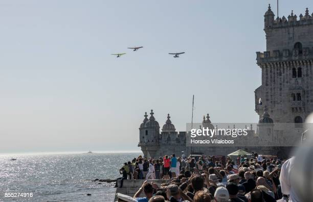 Spectators watch ultralight airplanes flying over Belem Tower during the commemoration of the 100th anniversary of Portuguese Naval Aviation on...