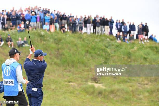 Spectators watch US golfer Bryson DeChambeau play his approach from the 5th fairway during a practice round for The 149th British Open Golf...