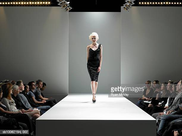 spectators watching fashion model on catwalk - fashion show stock pictures, royalty-free photos & images