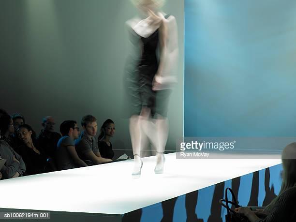 Spectators watching fashion model on catwalk