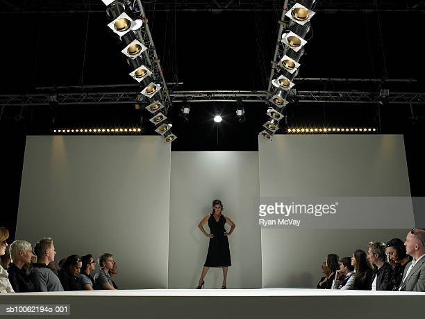 Spectators watching fashion model on catwalk