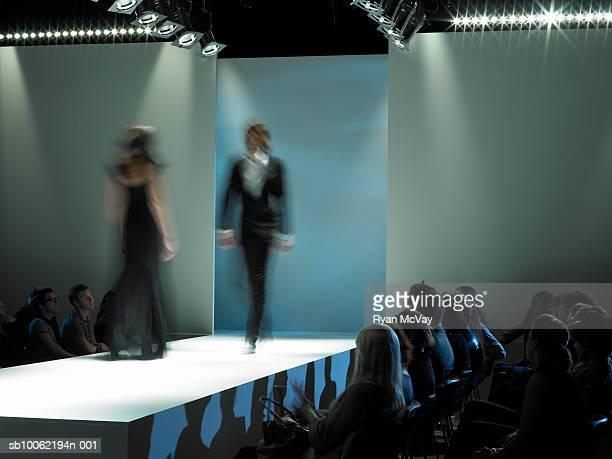 spectators watching fashion models on catwalk - catwalk stock pictures, royalty-free photos & images