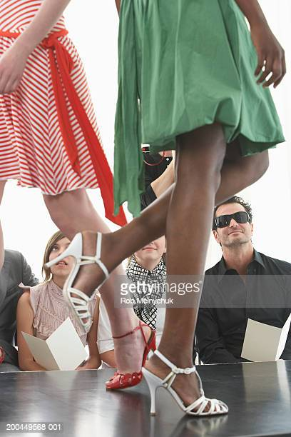 Spectators watching models on runway during fashion show