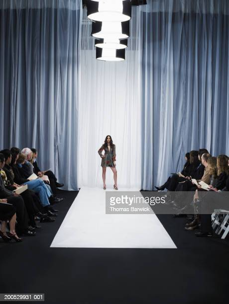 spectators watching young female model standing on catwalk - modeshow stockfoto's en -beelden