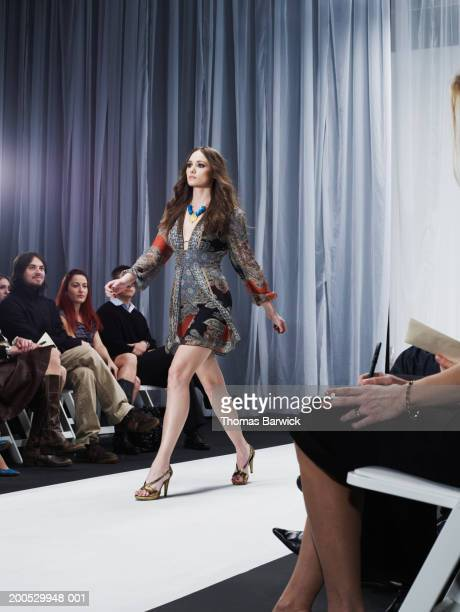 spectators watching young female model walk down catwalk - fashion runway stock pictures, royalty-free photos & images