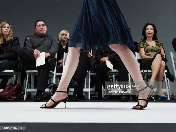 Spectators watching young female model walk down catwalk