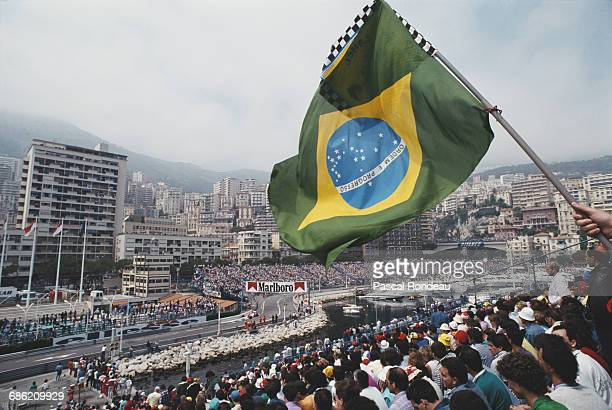 Spectators wave a Brazilian flag from the grandstand overlooking the harbour as Ayrton Senna of Brazil drives the Honda Marlboro McLaren McLaren MP45...