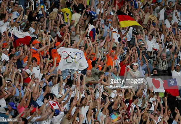 Spectators wave flags during the opening ceremony of the Athens 2004 Summer Olympic Games on August 13 2004 at the Sports Complex Olympic Stadium in...