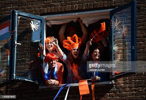 Spectators wave from a window to Dutch Queen Beatrix of the Netherlands during the traditional Queens Day celebrations on April 30, 2012 in Rhenen,...