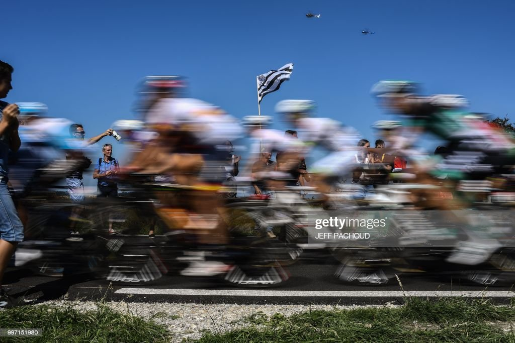 TOPSHOT - Spectators wave the flag of Brittany as riders speed following their first ascend of the Mur-de-Bretagne hill during the sixth stage of the 105th edition of the Tour de France cycling race between Brest and Mur-de-Bretagne Guerledan, western France, on July 12, 2018.