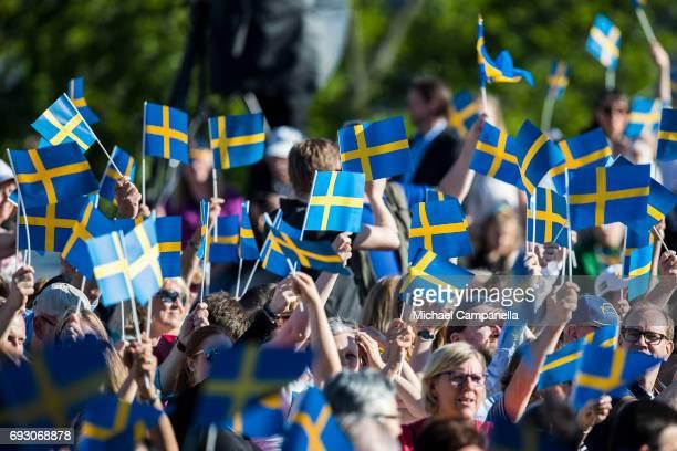 Spectators wave the Swedish flag during the national day celebrations at Skansen on June 6 2017 in Stockholm Sweden