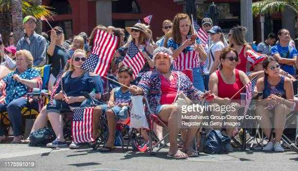 Spectators wave their flags as they sit along Main Street in Huntington Beach and watch the 115th annual Fourth of July parade on Thursday morning,...