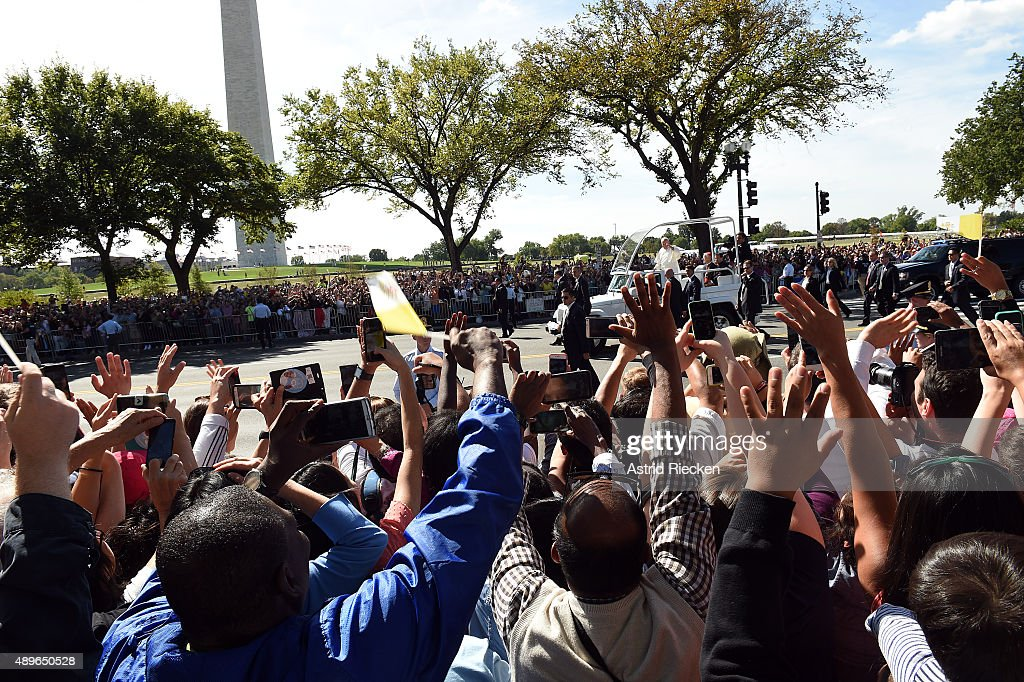 Spectators wave to Pope Francis during a parade on the streets around the Ellipse, south of the White House, September 23, 2015 in Washington, DC. Thousands of people gathered near the Ellipse to catch a glimpse of Pope Francis after he addressed an audience of 15,000 invited guests on the South Lawn of the White House during an official arrival ceremony with President Barack Obama. The Pope began his first trip to the United States at the White House followed by a visit to St. Matthew's Cathedral, and will then hold a Mass on the grounds of the Basilica of the National Shrine of the Immaculate Conception.