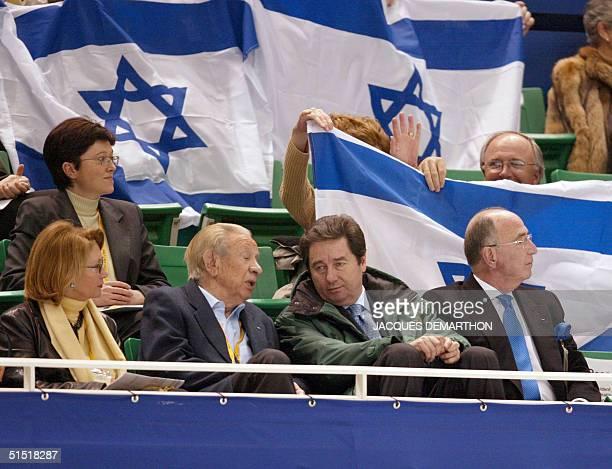 Spectators wave with the Israeli flag behind former IOC president Juan Antonio Samaranch International Skating Union president Ottavio Cinquanta and...