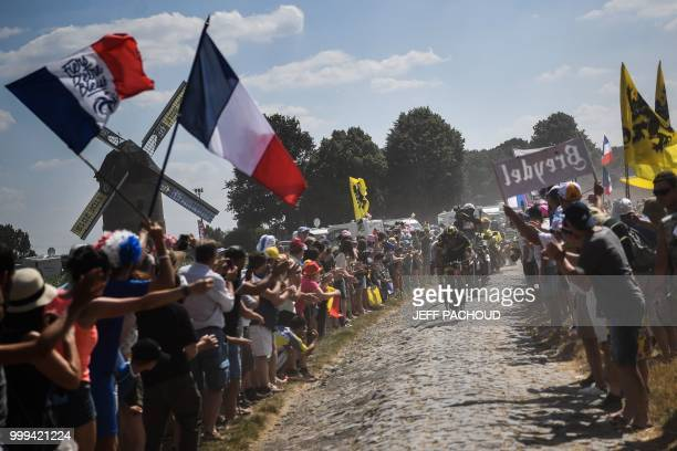 TOPSHOT The pack rides through a cobblestone section during the ninth stage of the 105th edition of the Tour de France cycling race between Arras and...
