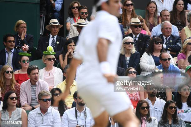 Spectators wear novelty tennis hats in the crowd as they watch Switzerland's Roger Federer play against Serbia's Novak Djokovic during the men's...