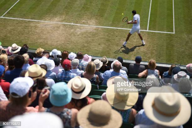Spectators wear sun hats as they watch Bulgaria's Grigor Dimitrov return to Cyprus's Marcos Baghdatis during their men's singles second round match...