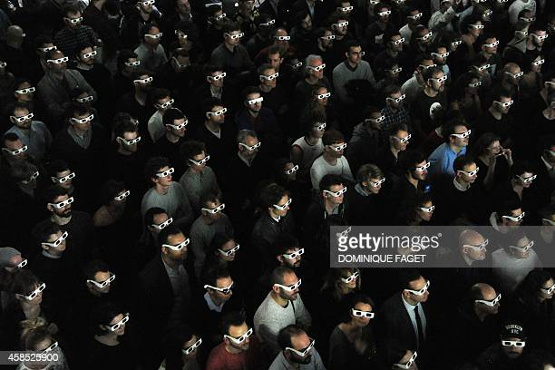 Spectators wearing 3D glasses watch the live concert of the German band Kraftwerk on November 6 2014 at the Louis Vuitton Art Foundation in Paris...