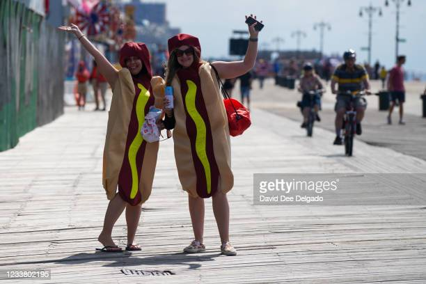 Spectators wearing hot dog costumes walk on the boardwalk prior to the 2021 Nathan's Famous 4th Of July International Hot Dog Eating Contest on July...