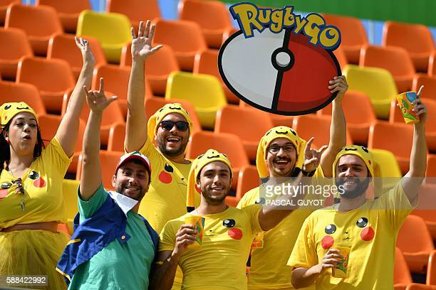 TOPSHOT Spectators wearing Pikachu tshirts the popular animation Pokemon series character attend the mens rugby sevens tournament during the Rio 2016...