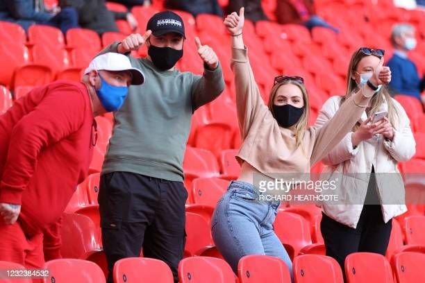 Spectators wearing protective face coverings to combat the spread of the coronavirus, take their seats for the English FA Cup semi-final football...