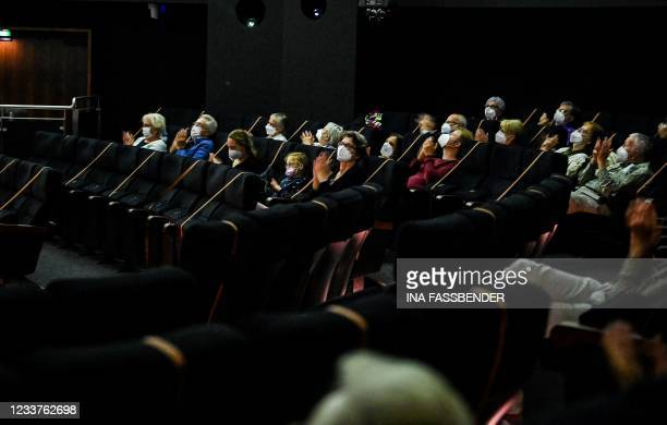 Spectators wearing protective face masks applaud following a concert and a presentation of photos by artist Heinrich Brinkmoeller-Becker on the...