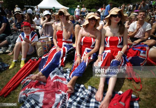 Spectators wearing Union flag decorated dresses gather on the outside viewing area known as 'Murray Mound' to watch the action on a giant TV screen...