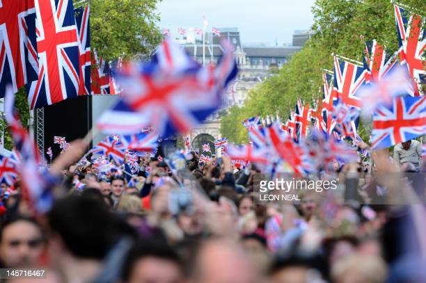 Spectators with Union Flags crowd the Mall waiting for the start of the Queen's Diamond Jubilee Concert at Buckingham Palace in London on June 4 2012...