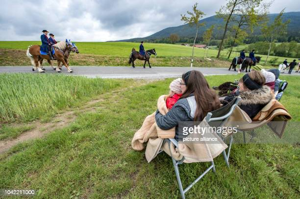 Spectators wrapped in blankets watch participants in the Koetzing Pentecost Ride ride their horses near Bad Koetzing Germany 16 May 2016 The...