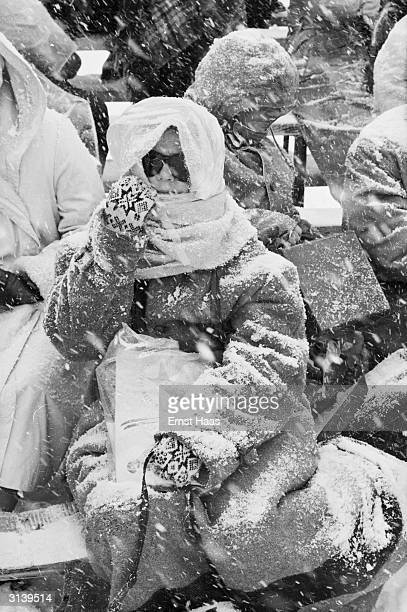 Spectators wrapped up against the terrible weather conditions at Squaw Valley California during the Winter Olympics