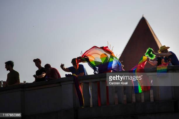 Spectatos wave while revelers stand on passenger ships while they attend the annual Christopher Street Day boat parade on July 25 2019 in Berlin...