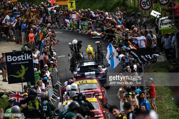 Specttaors cheer as Great Britain's Geraint Thomas, wearing the overall leader's yellow jersey , rides during the 20th stage of the 105th edition of...