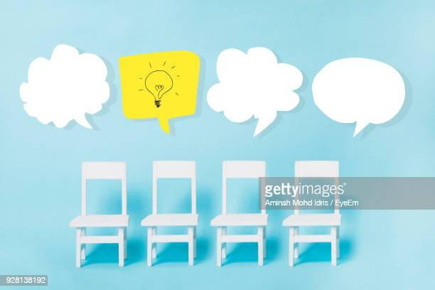 Speech Bubbles With Chairs Against Blue Background