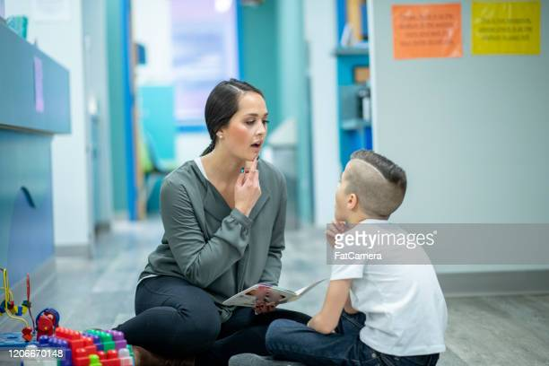 speech therapist sitting with a child stock photo - illness stock pictures, royalty-free photos & images