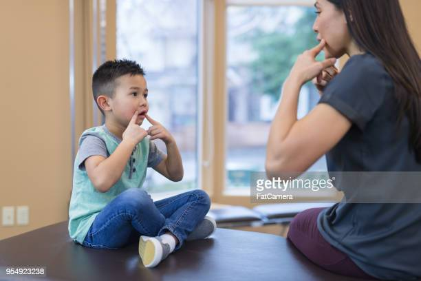 speech therapist works with a young ethnic boy - speech stock pictures, royalty-free photos & images